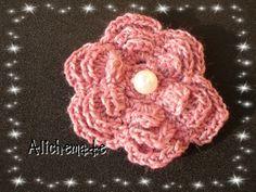 Broche en forma de flor, rosa, con una perla en el centro. €8