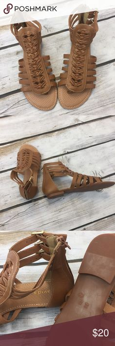 Gladiator Sandals Tan gladiator sandals. Has a zipper in the back that is gold. Has three little buckles on the outer ankle. This sandal is also has a strap like flip flops that go between your big toe and second toe. These are new, never worn, no tags, but come with a little dust bag Shoes Sandals