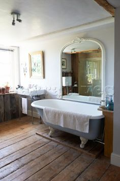 Large arched mirror above freestanding rolltop bath Iden farmhouse  Rye  East Sussex  UK