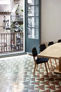 Triangular floor tiles gradually change colour from green to red inside this renovated Barcelona apartment