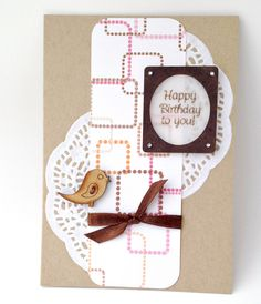 Birthday Card made using Kraft card stock, glittery scrapbook paper, paper doily, a laser cut frame, stamped vellum sentiment (ODBD stamp),  brown satin ribbon knot and tiny adhesive gems embellishments.