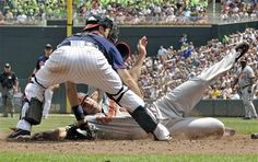 Baltimore Orioles' Chris Davis slides in to score as he beats the tag by Minnesota Twins catcher Joe Mauer, left, after third baseman Trevor Plouffe's throwing error to Mauer in the seventh inning of a baseball game, Thursday, July 19, 2012