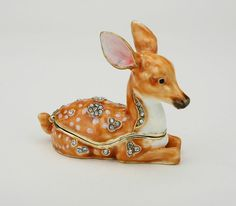 - Fawn figurine is also a box! Opens to reveal a storage compartment that's been completely finished in a glossy enamel. - 3 inches. Hand painted treasure is set with Swarovski Crystals and meticulous