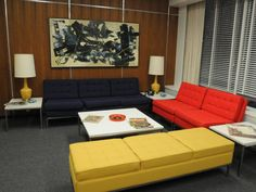 the reception area has a trio of mid-century modern sofas in solid, primary colors.