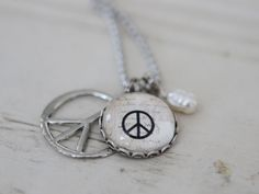 This adorable charm features a peace sign silhouetted against vintage paper.