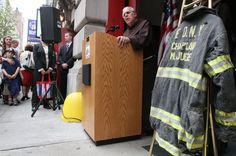 The bunker coat worn by FDNY Chaplain Mychal Judge is seen on view as Father Christopher Keenan, FDNY Chaplain, at the podium, speaks Sunday Sept. 11, 2011 at the New York City Fire Museum in New York during a memorial ceremony for the 343 members of the FDNY who lost their lives in the World Trade Center attacks. The bunker coat and helmet worn by Father Judge on 9/11, when he lost his life, were dedicated to the museum during the service. (AP Photo/Tina Fineberg)