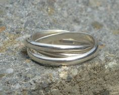 Three sterling silver bands are linked together to create this Russian wedding ring, and can be said to represent the trinity. Also a really nice gift for the new mother, symbolizing the new family: mother, father and baby. Take a look at my Etsy page to see my other rings: http://www.etsy.com/nl/shop/Cinsier?section_id=13790924