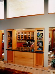 Spacious contemporary style kitchen shown with fir wood, accented with stainless steel and granite counter tops, unique show-through cabinet drawers and large eat in bar. Secondary view showing the opposite side of the large eat in bar.