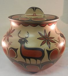 This gorgeous vessel was made by very well known #SantoDomingo potter Vidal Aguilar. The lovely lidded storage jar features a polychrome deer and floral motif. The earth tone colors give the piece a rustic, yet contemporary feel. The lid is also decorated with a beautiful swirling geometric patterns that perfectly caps off the vessel.