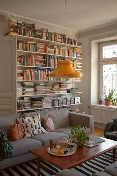 grey sofa, striped rugs, wall shelves