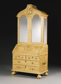 "A George I gilt-gesso bureau-cabinet, circa 1720, attributed to James Moore,  the gilt surface decorated overall with strap-work and foliage patterns, pointed arched moulded cornice with a carved shell motif...fall front desk with fitted interior with pigeonholes & drawers also yew veneered,  above  lower section with two short & three long drawers, sides with carrying handles, all raised on boldly carved paw feet;   7'-10"" H, 3'-11"" W, 2' D."