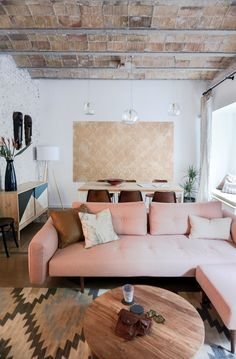 To make the space feel brighter, all of the walls—even bricks—are painted white, which contrasts with the raw brick ceiling and original brown tile floors. The Recast Plus sofa bed, with a pink hue that echoes the brick ceiling, is from Innovation Living. The blown-glass Gordiola pendants are a design the resident saw in a Mallorca hotel that Bloomint designed.