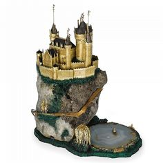 "AN ENGLISH GOLD, SILVER AND MINERAL SPECIMAN ""FAIRY TALE"" CASTLE, WILLIAM TOLLIDAY, LONDON, CIRCA 1980 mounted on a rocky mountain of rock crystal with pyrite inclusion, all on a faux malachite base, the many turreted castle of gold with oxidized silver roofs, complete with draw bridge, a knight in armor approaching on a serpentine gold path, strewn with diamond-set flowers, at the base a fisherman in a boat, floating on a striated agate pond with willow tree at one side signed on gold ..."
