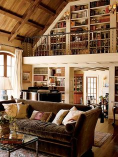 At the end of this living room, a full-height library wall includes balcony access. The book-lined wall, wood ceiling, and wide-plank floor give the room visual warmth.