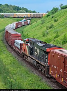 North American economy on the move. CN 369's mid train remote is seen in full throttle helping with the full on assault of the York Sub grade meanwhile CP241's freight rolls by over top.