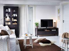 Soggiorno con divano a 3 posti bianco, set di tavolini, mobile TV marrone-nero e vetrina con cassetti.
