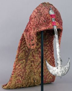 Indian (South) cloth covered riveted mail zirah kulah (coif), with nasel, 17th century, possibly 16th century, iron alloy, textile (velvet), silver. H. including nape defense 21 in. (53.5 cm); H. including nasal 14 1/2 in. (36.8 cm); H. excluding nape defense and nasal 9 1/2 in. (24.1 cm); W. 12 1/4 in. (31.1 cm); D. 7 3/4 in. (19.7 cm); Wt. 5 lb. 6.7 oz. (2457.9 g), Bequest of George C. Stone, 1935, Met Museum.