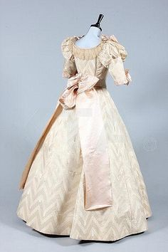 An ivory damask ball/bridal gown, circa 1895, the bodice with puffed upper sleeves adorned with pink satin ribbons, matching skirt with chevron and ellipse repeats