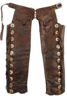 """These seamless leather pants have a shape that reminded one of a double-barreled shotgun, hence the name """"Shotgun Chaps. Typically they were held together by a belt that fit straight across the waist and often were decorated along the outside seam with long fringe. The chaps that didn't have a fringe were called """"closed-leg"""" chaps."""