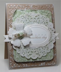 •the inking was done with white craft ink direct to paper on both the card base and the embossed layer. •the flower contains 3 layers. The top is vellum that was die cut, then embossed. It is layered over 2 white die cut flowers. •The doily is not a die cut, it was purchased at AC Moore in the baking section
