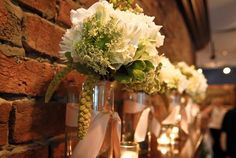 Pretty Maids All in a Row....Textural white, green and cream bouquets banded in a sash of pecan satin ribbon.