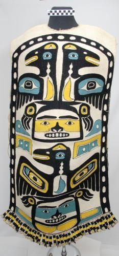 Tlingit tunic Place: Haines. Date collected: 1931. Material: mountain goat wool, cedar bark, wood dowels in fringes . Width: 70cm. Length: 123cm.