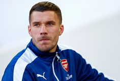 Lukas Podolski of Arsenal takes his seat on the bench before the Barclays Premier League match between West Ham United and Arsenal at Boleyn Ground on December 28, 2014 in London, England