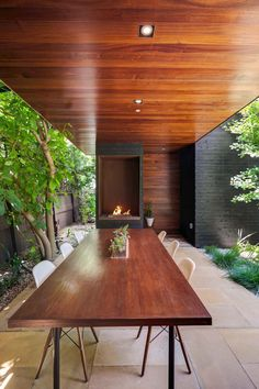 Holz in warmen Nuancen und Naturstein in der überdachten Terrasse