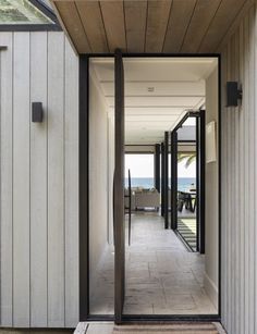 Sitting on fairly public site, this Waiheke Island holiday used clever design and thoughtful material choices to quietly slip from view Cedar Cladding, Waiheke Island, Timber Door, Solid Doors, Storey Homes, The Gables, Big Windows, Stone Flooring, Prefab