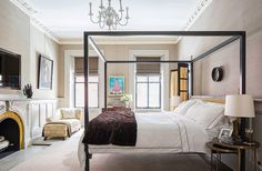 A contemporary black canopy bed frame adds modern contrast this this glamorous master bedroom.