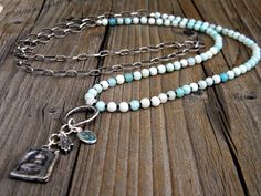 Long Boho Necklace, Petite Blue Amazonite Beads, Loopy Silver Chain, Bohemian Necklace, Amulet Buddha, Aqua Dangle, Hamsa  This 40 long boho necklace has been made with beautiful, petite Amazonite beads and matte brown seed beads, lovely loopy antique silver tone chain, leading to an amulet with an awesome Buddha, gorgeous little faceted Aqua stone and dangling little hamsa. It is perfect for all seasons of the year, and pretty enough to wear alone, or layer up. This piece will arrive in a…