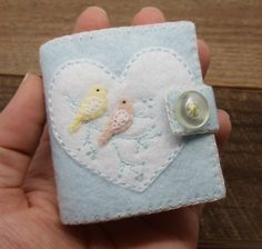 **NO LONGER ACCEPTING CUSTOM ORDERS OR ORDERS FOR PERSONALIZATION** This little needle book was all hand stitched, embroidered, and appliqued using the teeniest pieces of felt and even teenier stitches!  It features a pale baby blue felt cover, a big white heart, and two tiny yellow and peach colored love birds perched in the branches of a tree. There are 4 pages of coordinating yellow and peach felt to safely hold your pins and needles.  Closes securely with a snap. (Vintage button is…