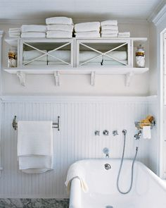 A wooden flea-market cupboard makes a great towel cabinet. Use the top of the cabinet for extra storage. Keep your regular supply in the glass-fronted cabinet. Having all towels visible makes it easy to keep track of your inventory. Open shelves on the sides hold glass jars full of cotton balls and soaps.