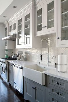 Grey/white kitchen w/ dark wood floors. Farmhouse sink.