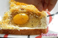 sprinkling cheese onto the egg toast
