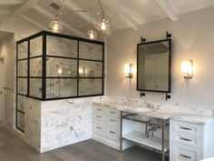 A custom mirror inspired by our Collector's Shelving System looks amazing in this master bathroom! An industrial chic look with a classic pallet.