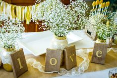 Vintage theme with baby breath centerpieces. Mason jars and maybe one or two batches of babys breath depending on your party size. Top it off with little accents like these l-o-v-e signs.