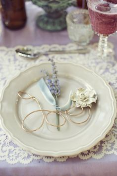Lavender stems tied in ribbon and a book page paper flower embellish the guest's name written in wire...a unique place setting