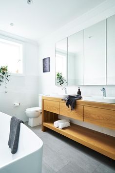 Featuring a custom oak vanity with Caroma sinks and bath and large-format floor tiles from Better Tiles, this bathroom is ideal for a growing family. Photo: John Paul Urizar | Styling: Helen Carter | Story: Australian House & Garden #bathroom