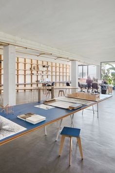 Barcelona warehouse transformed into flexible co-working space for architects and designers wood table, blue, shelve, Exposed concrete