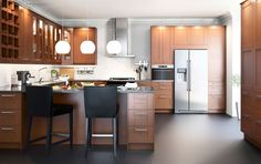 A large kitchen with medium brown drawers, doors, glass doors and dark countertops. Space for chairs
