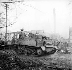 Universal carriers of the 4th King's Shropshire Light Infantry, 11th Armoured Division, pass through the burning village of Levern, 4 April 1945.