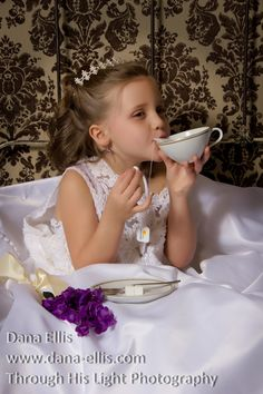 This is one of our younger models.  Is there anything better than wearing your mom's wedding dress, sipping on fake tea and eating sugar cubes?  I think not!  I added a tiara and pulled her hair up around the back with soft curls for a little princess look.  The china is antique as is the bed frame behind her giving the whole theme a vintage feel.  I added flowers for a touch of color.      The main light was a strobe and window light was our fill.