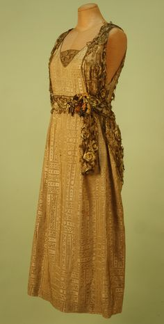 Evening Gown: ca. 1912, metallic brocade, woven foliate stripes with applied lace on bodice creating bolero effect with peplum, waistband decorated with cloth flowers, net and lace net insert.