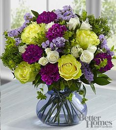 1st Anniversary Flower - Carnation This bouquet includes green roses, white spray roses, purple carnations, lavender carnations, lavender statice, and an assortment of lush greens with a purple glass vase.