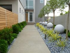 Walkway to Contemporary Home Lined With Neat Landscaping