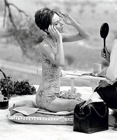 Audrey Hepburn, photographed by Terry O'Neill, checking her hair and makeup poolside during the filming of Two For the Road in St Tropez, September 1966.