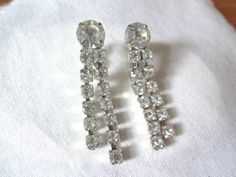 """These unmarked beauties are in excellent condition and have two rows of dangling rhinestones hanging from a center larger prong set round stone. One row is slightly longer and have a drop of about 1 7/8"""", and the larger rhinestone is 3/8"""" diameter. Set..."""