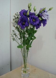 91- Vaso pequeno com Lisianthus azuis e folhagem.
