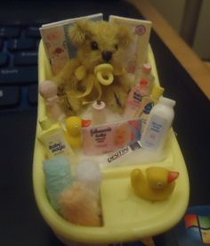 A miniature baby tub filled with gifts for baby and mom.